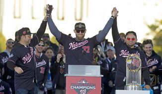 Washington Nationals pitcher and World Series MVP Stephen Strasburg, celebrates the World Series baseball championship during a rally following a parade to celebrate the team's World Series baseball championship over Houston Astros, Saturday, Nov. 2, 2019, in Washington. Nationals right fielder Gerardo Parra is right and pitcher Anibal Sanchez, left.  (AP Photo/Jose Luis Magana)