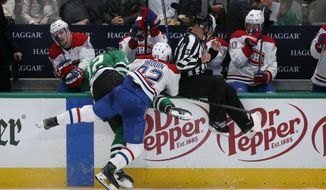 Dallas Stars center Radek Faksa (12) gets pushed into the Canadiens bench by Montreal Canadiens left wing Jonathan Drouin (92) during the second period of an NHL hockey game in Dallas, Saturday, Nov. 2, 2019. (AP Photo/Michael Ainsworth)