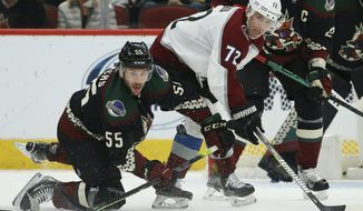 Arizona Coyotes defenseman Jason Demers (55) looks to control the puck as he collides with Colorado Avalanche right wing Joonas Donskoi (72) during the second period of an NHL hockey game Saturday, Nov. 2, 2019, in Glendale, Ariz. (AP Photo/Ross D. Franklin)