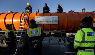 In this Monday, Jan. 13, 2014 file photo, police prepare to remove a protestor from the top of a vehicle waiting to enter an exploratory drill site for the controversial gas extraction process known as fracking at Barton Moss in Manchester, England. The British government announced Saturday, Nov. 2, 2019, that it will no longer allow fracking because of new scientific analysis that casts doubts on the safety of the controversial practice, but some critics said the measure falls short because it is not a permanent ban. (AP Photo/Jon Super, File)