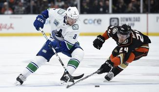 Anaheim Ducks right wing Carter Rowney, right, reaches for the puck handled by Vancouver Canucks center J.T. Miller during the first period of an NHL hockey game in Anaheim, Calif., Friday, Nov. 1, 2019. (AP Photo/Kelvin Kuo)
