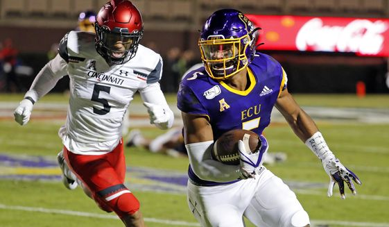 East Carolina's C.J. Johnson, right, runs the ball after a catch with Cincinnati's Darrick Forrest (5) pursuing during the first half of an NCAA college football game in Greenville, N.C., Saturday, Nov. 2, 2019. (AP Photo/Karl B DeBlaker)