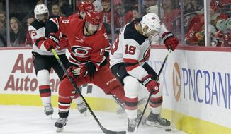 Carolina Hurricanes left wing Warren Foegele (13) and New Jersey Devils center Travis Zajac (19) struggle for possession of the puck during the first period of an NHL hockey game in Raleigh, N.C., Saturday, Nov. 2, 2019. (AP Photo/Gerry Broome)