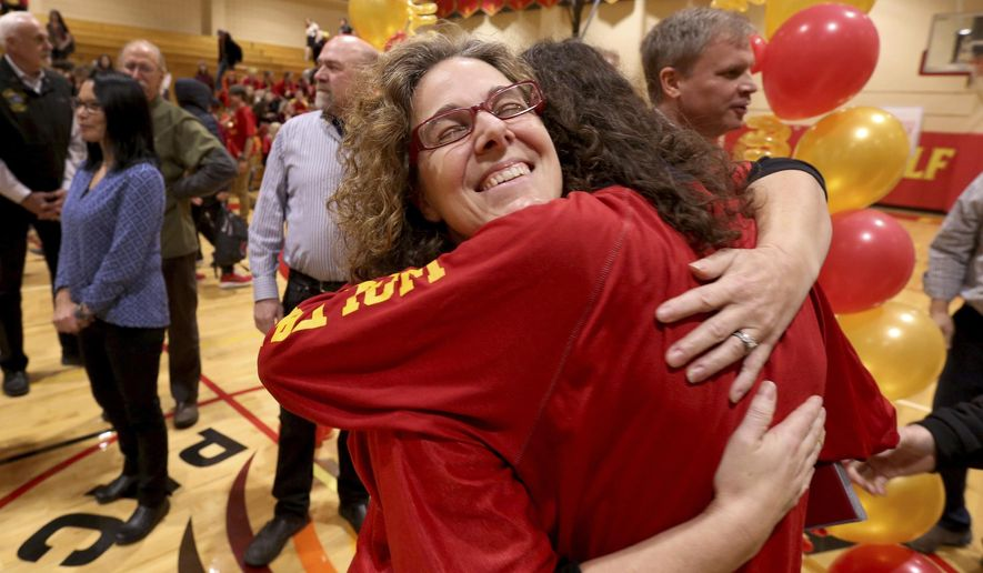 In this Friday, Oct. 25, 2019 photo, West Valley High School teacher Amy Galloway is congratulated by a student after being named the 2020 Alaska Teacher of the Year during an assembly in the school gymnasium in Fairbanks, Alaska. (Eric Engman/Fairbanks Daily News-Miner via AP)