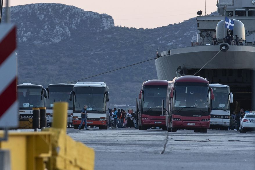 Migrants wait to board on buses after their disembarkation at the port of Elefsina, near Athens, on Saturday, Nov. 2, 2019. The transfer of migrants from overcrowded camps on the islands to the Greek mainland continued this weekend, with 415 arriving Saturday afternoon at the port of Elefsina west of Athens and at least another 400 expected Sunday or early Monday. (AP Photo/Yorgos Karahalis)