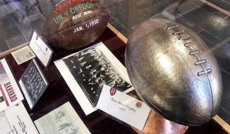 A selection memorabilia from the 1920 Harvard University football season, including a dated leather football, a team photo and trophy, are displayed at the school's athletic complex in Cambridge, Mass., Friday Nov. 1, 2019. Harvard's 7-6 victory over Oregon in the Jan. 1, 1920, Tournament East-West Football Game, a precursor to the Rose Bowl, was the only postseason appearance in the Ivy League school's century and a half of football. (AP Photo/Jimmy Golen)