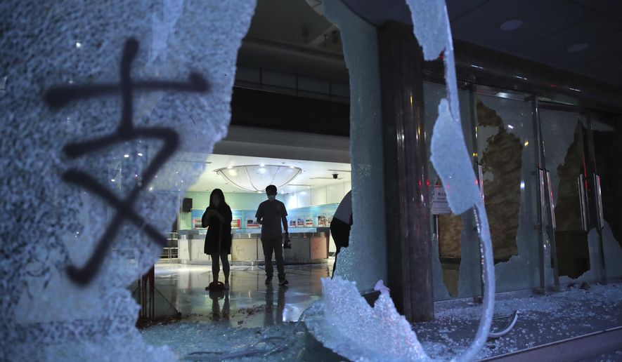 People stand in the lobby of the offices of China's Xinhua News Agency damaged by protesters in Hong Kong, Saturday, Nov. 2, 2019. Hong Kong riot police fired multiple rounds of tear gas and used a water cannon Saturday to break up a rally by thousands of masked protesters demanding meaningful autonomy after Beijing indicated it could tighten its grip on the Chinese territory. (AP Photo/Kin Cheung)