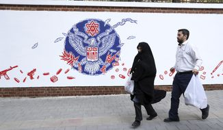 People walk past a satirical drawing of the Great Seal of the United States after new anti-U.S. murals on the walls of former U.S. embassy unveiled in a ceremony in Tehran, Iran, Saturday, Nov. 2, 2019. Anti-U.S. works of graphics is the main theme of the wall murals painted by a team of artists ahead of the 40th anniversary of the takeover of the U.S. diplomatic post by revolutionary students. (AP Photo/Vahid Salemi)