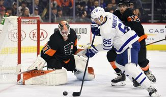 Philadelphia Flyers goaltender Brian Elliott, left, looks for the puck as Toronto Maple Leafs' Ilya Mikheyev (65) takes a shot past the defense of Matt Niskanen (15) during the first period of an NHL hockey game, Saturday, Nov. 2, 2019, in Philadelphia. (AP Photo/Derik Hamilton)