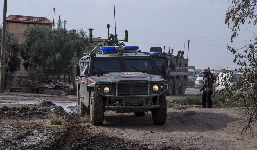 Turkish and Russian patrol is seen near the town of Darbasiyah, Syria, Friday, Nov. 1, 2019. Turkey and Russia launched joint patrols Friday in northeastern Syria, under a deal that halted a Turkish offensive against Syrian Kurdish fighters who were forced to withdraw from the border area following Ankara's incursion.(AP Photo/Baderkhan Ahmad)