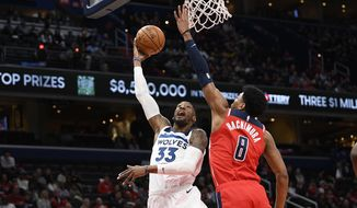 Minnesota Timberwolves forward Robert Covington (33) goes to the basket next to Washington Wizards forward Rui Hachimura (8) during the first half of an NBA basketball game Saturday, Nov. 2, 2019, in Washington. (AP Photo/Nick Wass) ** FILE **