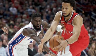 Philadelphia 76ers forward James Ennis III, left, and Portland Trail Blazers forward Skal Labissiere reach for the ball during the first half of an NBA basketball game in Portland, Ore., Saturday, Nov. 2, 2019. (AP Photo/Craig Mitchelldyer)