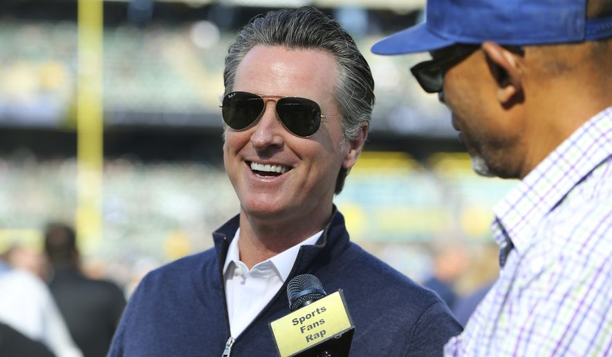 Gov. Gavin Newsom is interviewed before an NFL football game between the Oakland Raiders and the Detroit Lions in Oakland, Calif., Sunday, Nov. 3, 2019. Mr. Newsom took to Twitter on Nov. 3 to say President Trump should be 'excused' from conversations about combating the state's wildfires because the president doesn't believe in manmade climate change.  (AP Photo/John Hefti)