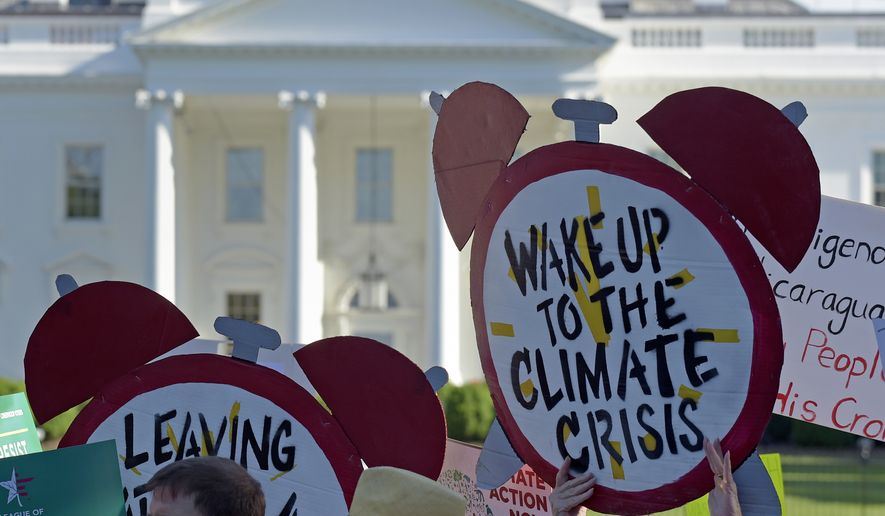 In this June 1, 2017, photo, protesters gather outside the White House in Washington to protest President Donald Trump's decision to withdraw the United States from the Paris climate change accord. (AP Photo/Susan Walsh) **FILE**