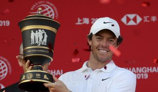 Rory McIlroy of Northern Ireland raises the trophy after winning the HSBC Champions golf tournament at the Sheshan International Golf Club in Shanghai on Sunday, Nov. 3, 2019. (AP Photo/Ng Han Guan)