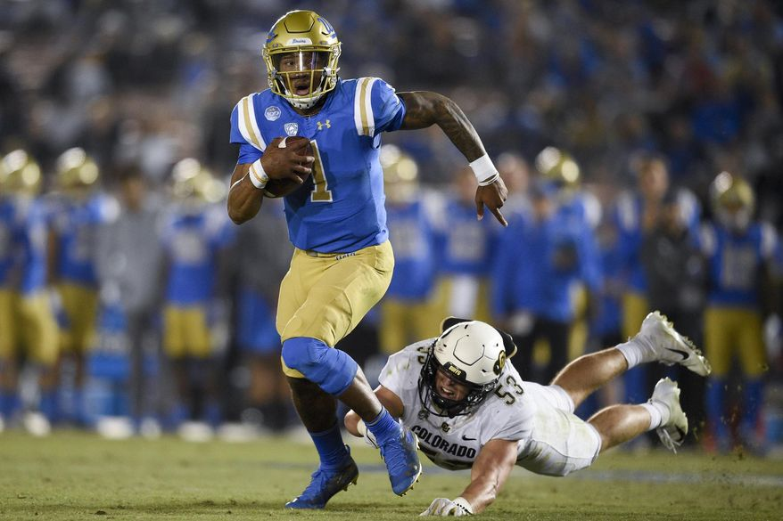 UCLA quarterback Dorian Thompson-Robinson, left, runs while pursued by Colorado linebacker Nate Landman during the first half of an NCAA college football game in Los Angeles, Saturday, Nov. 2, 2019. (AP Photo/Kelvin Kuo)