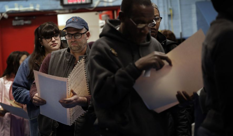 In this Nov. 6, 2018 file photo, voters read their ballot papers as they wait in line to cast their vote at P.S. 161 in Brooklyn borough of New York. A ballot measure will give New York City residents a chance to institute ranked choice voting in primaries and special elections. Under the system now in effect in cities such as San Francisco and Cambridge, Massachusetts as well as the entire state of Maine, voters can rank candidates in order of preference instead of choosing just one.(AP Photo/Wong Maye-E, File)