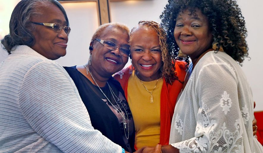Maxine Bryant, 60, second from right, stands with her sisters at Scott United Methodist Church, Sunday, Oct. 13, 2019. Adopted as a child, she was reunited with her siblings after 60 years. Her sisters are Donzella Triplett, 69, from left, Birdie Peoples Ferguson, and Victoria Peoples, 67, right (Kelly Wilkinson/The Indianapolis Star via AP)