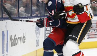 Columbus Blue Jackets' Scott Harrington, left, fights off a check from Calgary Flames' Milan Lucic during the first period of an NHL hockey game Saturday, Nov. 2, 2019, in Columbus, Ohio. (AP Photo/Jay LaPrete)