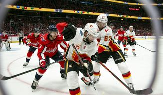 Calgary Flames center Tobias Rieder (16), from Germany, looks for an open teammate as right wing Michael Frolik (67), of the Czech Republic, fends off Washington Capitals defenseman Nick Jensen (3) during the second period of an NHL hockey game Sunday, Nov. 3, 2019, in Washington. (AP Photo/Al Drago)