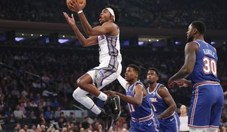 Sacramento Kings guard De'Aaron Fox (5) goes up for two points as New York Knicks guard Frank Ntilikina (11), center Bobby Portis (1) and forward Julius Randle (30) watch from the floor during the first half of an NBA basketball game in New York, Sunday, Nov. 3, 2019. (AP Photo/Kathy Willens)