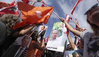 Supporters of Lebanese President Michel Aoun hold his pictures and Lebanese flags during a protest near the presidential palace in the Beirut suburb of Baabda, Lebanon, Sunday, Nov. 3, 2019. Thousands of people are marching to show their support for Aoun and his proposed political reforms that come after more than two weeks of widespread anti-government demonstrations. (AP Photo/Hassan Ammar)
