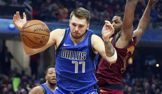 Dallas Mavericks' Luka Doncic (77) battles Cleveland Cavaliers' Tristan Thompson for a rebound in the first half of an NBA basketball game, Sunday, Nov. 3, 2019, in Cleveland. (AP Photo/Ron Schwane)