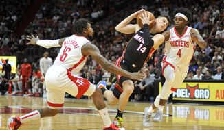 Miami Heat guard Tyler Herro (14) drives to the net against Houston Rockets guard Ben McLemore (16) and forward Danuel House Jr. (4) during the first half of an NBA basketball game, Sunday, Nov. 3, 2019, in Miami. (AP Photo/Gaston De Cardenas)