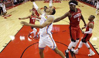 Oklahoma City Thunder forward Darius Bazley, center, shoots as Houston Rockets forward Danuel House Jr. (4) defends during the second half of an NBA basketball game, Monday, Oct. 28, 2019, in Houston. (AP Photo/Eric Christian Smith)