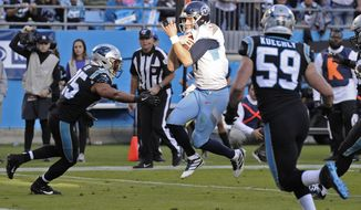 Tennessee Titans quarterback Ryan Tannehill, center, runs into the end zone for a touchdown while Carolina Panthers middle linebacker Luke Kuechly (59) ands strong safety Eric Reid, left, defend during the second half of an NFL football game in Charlotte, N.C., Sunday, Nov. 3, 2019. (AP Photo/Mike McCarn)