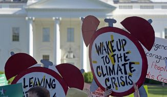 In this June 1, 2017, file photo, protesters gather outside the White House in Washington to protest President Donald Trump's decision to withdraw the United States from the Paris climate change accord. (AP Photo/Susan Walsh)