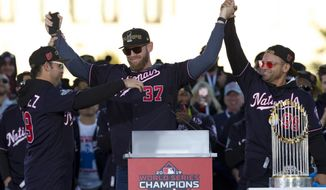 Washington Nationals pitcher Stephen Strasburg, center, celebrates with teammates Anibal Sanchez, left, and Gerardo Parra during a rally following a parade to celebrate the team's World Series baseball championship over the Houston Astros, Saturday, Nov. 2, 2019, in Washington. (AP Photo/Jose Luis Magana)