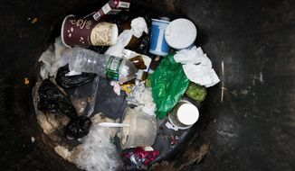 A plastic water bottle and plastic bags are seen discarded with other garbage in a corner trash can in the East Village neighborhood of Manhattan, Wednesday, March 27, 2019 in New York. Two New York lawmakers say Wednesday that they're optimistic that a ban on single-use plastic shopping bags could be included in the spending plan that's due Sunday. (AP Photo/Mary Altaffer)