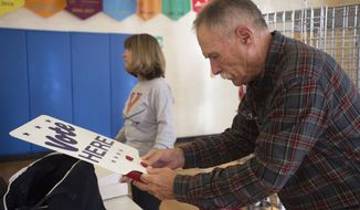 "Harry Ford, right, puts together a ""vote here"" sign at a polling station set up at Boonsboro Elementary School in Bedford, Va., Monday, Nov. 4, 2019. Several people helped set up the polling station in preparation for election day Tuesday. (Taylor Irby/The News & Advance via AP)"