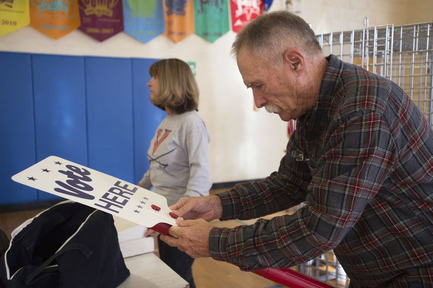 """Harry Ford, right, puts together a """"vote here"""" sign at a polling station set up at Boonsboro Elementary School in Bedford, Va., Monday, Nov. 4, 2019. Several people helped set up the polling station in preparation for election day Tuesday. (Taylor Irby/The News & Advance via AP)"""