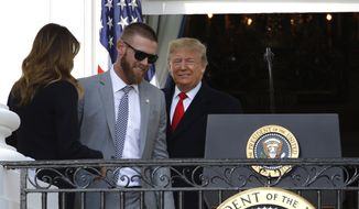 President Donald Trump invites Washington Nationals starting pitcher Stephen Strasburg, second from left, to speak at the podium during an event to honor the 2019 World Series champion Nationals baseball team at the White House, Monday, Nov. 4, 2019, in Washington, as first lady Melania Trump watches. (AP Photo/Patrick Semansky)