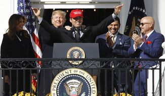 President Donald Trump stands with Washington Nationals catcher Kurt Suzuki, during an event to honor the 2019 World Series champion Washington Nationals on the balcony of the White House, Monday, Nov. 4, 2019, in Washington, as First Lady Melania Trump, left, and Washington Nationals coach Dave Martinez, second from right and general manager Mike Rizzo, far right, look on. Suzuki is wearing a Make America Great Again hat. (AP Photo/Patrick Semansky)