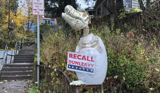 "In this Friday, Nov. 1, 2019, photo, a sign reading ""Recall Dunleavy"" hangs from a decoration in front of a yard near the Alaska governor's mansion in Juneau, Alaska. A fight is brewing in the state over whether Republican Gov. Mike Dunleavy should be recalled from office, with his critics saying he's incompetent and has recklessly tried to cut spending while supporters see a politically motivated attempt to undo the last election. (AP Photo/Becky Bohrer)"