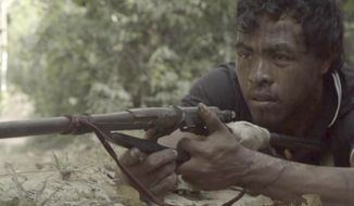 "In this Sept. 2019, video frame, Paulo Paulino Guajajara, a Forest Guardian protecting the Arariboia indigenous reserve poses with his makeshift weapon, at the reserve in Maranhao state, Brazil. The 26-year-old Guajajara was killed in an ambush by illegal loggers on Friday, Nov. 1, 2019. ""My son fought and died. He died for all of us here, defending this area,"" Paulo's father Ze Maria Paulino Guajajara said. (Documentary Iwazayzar - Guardioes da Natureza via AP)"