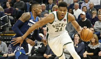 Milwaukee Bucks' Giannis Antetokounmpo, right, of Greece, drives around Minnesota Timberwolves' Robert Covington in the first half of an NBA basketball game Monday, Nov 4, 2019, in Minneapolis. (AP Photo/Jim Mone)