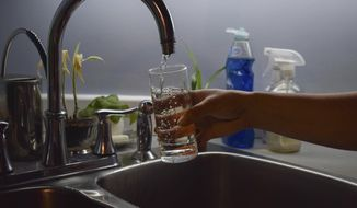 In this July 21, 2019, file photo, Florabela Cunha fills a glass of water from her kitchen faucet in Prince Rupert, British Columbia, Canada. In previous summers, she used to make iced tea for her family using water from her tap, but she has since stopped citing concerns about the water quality. Hundreds of thousands of Canadians from coast to coast have been unwittingly exposed to levels of lead in their drinking water. (Mackenzie Lad/Institute for Investigative Journalism/Concordia University via AP)