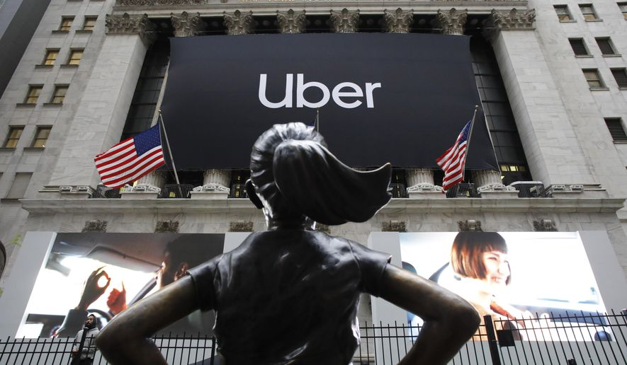 In this May 10, 2019, file photo the statue of Fearless Girl stands in front of the New York Stock Exchange before Uber holds its initial public offering. Uber reports financial results Monday, Nov. 4. (AP Photo/Mark Lennihan, File)