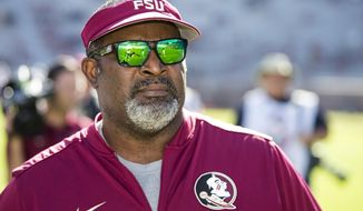 FILE - In this Dec. 2, 2017, file photo, Florida State interim head coach Odell Haggins watches the team warm up before an NCAA college football game Louisiana Monreo in Tallahassee, Fla. Florida State athletic director David Coburn says he would like to hire a national search firm and have a new head football coach before the end of the regular season. Until then the Seminoles have named Haggins as the interim head coach for the final three games. (AP Photo/Mark Wallheiser, File)