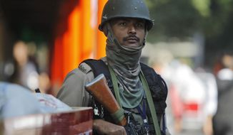 An Indian paramilitary soldier stands guard outside the civil secretariat of the Union territory of Jammu and Kashmir during the annual reopening of the former state's winter capital in Jammu, India, Monday, Nov. 4, 2019. India on Thursday formally implemented legislation that removes Indian-controlled Kashmir's semi-autonomous status and began direct federal rule. (AP Photo/Channi Anand)