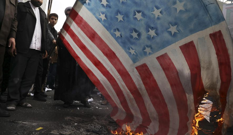 """Demonstrators set fire to a rendition of the U.S. flag during a rally in front of the former U.S. Embassy in Tehran, Iran, Monday, Nov. 4, 2019. Reviving decades-old cries of """"Death to America,"""" Iran on Monday marked the 40th anniversary of the 1979 student takeover of the U.S. Embassy in Tehran and the 444-day hostage crisis that followed as tensions remain high over the country's collapsing nuclear deal with world powers. (AP Photo/Vahid Salemi)"""