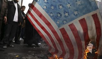 "Demonstrators set fire to a rendition of the U.S. flag during a rally in front of the former U.S. Embassy in Tehran, Iran, Monday, Nov. 4, 2019. Reviving decades-old cries of ""Death to America,"" Iran on Monday marked the 40th anniversary of the 1979 student takeover of the U.S. Embassy in Tehran and the 444-day hostage crisis that followed as tensions remain high over the country's collapsing nuclear deal with world powers. (AP Photo/Vahid Salemi)"