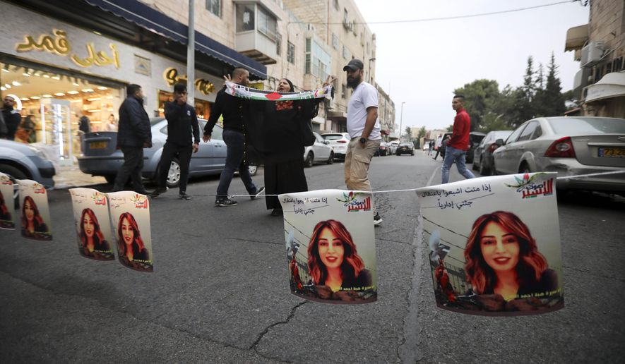 FILE - In a Saturday, Oct. 26, 2019 file photo, Palestinians hang photos of Heba al-Labadi, a Jordanian citizen of Palestinian descent, during a protest demanding her release in east Jerusalem. Israel and Jordan announced Monday, Nov. 4, 2019 they have agreed to release Heba al-Labadi and Abdul Rahman Miri, two young Jordanian women held by Israel without charges for over two months. (AP Photo/Mahmoud Illean, File)