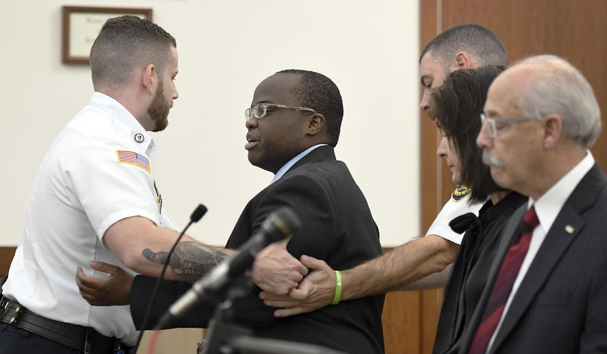 Defendant David Njuguna is removed from Worcester Superior Court in Worcester, Massachusetts after a rambling outburst before closing arguments were set to begin in his trial Tuesday, October 29, 2019. Njuguna is charged in a 2016 crash on the Massachusetts Turnpike in Charlton that claimed the life of Mass. State Trooper Thomas L. Clardy.(Rick Cinclair/Worcester Telegram & Gazette via AP)