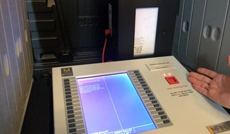 In this Sept. 25, 2019 photo, Indiana Secretary of State Connie Lawson demonstrates an upgraded voting machine on Wednesday, Sept. 25, 2019, at the Indiana Statehouse office in Indianapolis. (AP Photo/Tom Davies) **FILE**