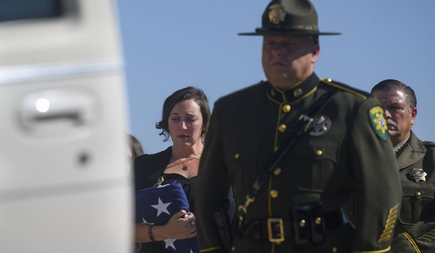 Katie Kregoski Ishmael, left, wife of fallen El Dorado County Sheriff's Deputy Brian Ishmael, holds a flag while her husband's casket is placed in a hearse at Bayside Adventure Church in Roseville, Calif., Tuesday, Nov. 5, 2019. El Dorado County Sheriff John D'Agostini stands at the far right. Friends, colleagues and family on Tuesday remembered a Northern California sheriff's deputy killed last month while responding to a call about a theft from a marijuana garden as a devoted father and a committed deputy. More than 3,000 people attended a service in honor of Deputy Ishmael. Blue ribbons were tied to the trees lining the road to the church, and adorned the doors leading to the church's sanctuary, The Sacramento Bee reported. (Daniel Kim/The Sacramento Bee via AP)